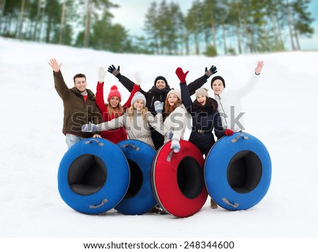 winter, leisure, sport, friendship and people concept - group of smiling friends with snow tubes waving hands outdoors - stock photo