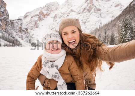 Winter leisure time spent outdoors among snowy peaks can turn the holidays into a fascinating journey. Mother and child taking selfie outdoors among snow-capped mountains