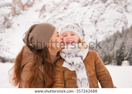 Winter leisure time spent outdoors among snowy peaks can turn the holidays into a fascinating journey. Portrait of mother kissing child outdoors among snow-capped mountains - stock photo
