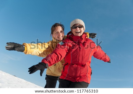 Winter lifestyle - happy smiling senior mother with her adult daughter in snow nature - stock photo