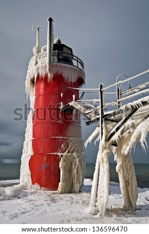 Winter Light A winter sun shines on an ice covered Great Lakes lighthouse at South Haven, Michigan. - stock photo
