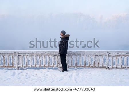 Winter man standing in front of the fence