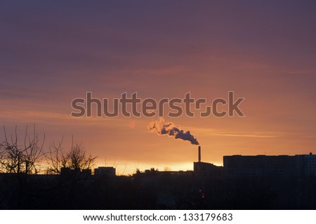 winter morning city skyline with chimney smoke cloud
