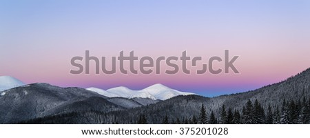 Winter morning panoramic view of snowy mountain peaks. Dawn. Soft light. Clear purple sky. Dark forest line - stock photo
