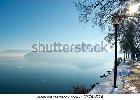 Winter morning walks near the frozen lake are very good for health, Kastoria, Greece. - stock photo