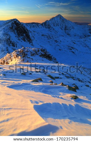 Winter mountain landscape with sunset light on the sky and snow  - stock photo