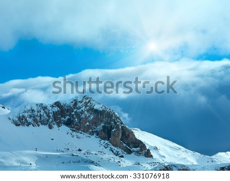 Winter mountain slope with ski track and cross on rock top (Austria). - stock photo