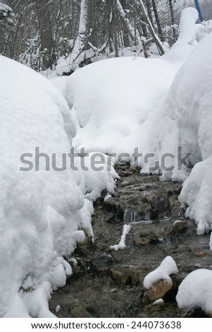 Winter mountain stream.  Mountain of Lake Baikal. Baykalsk, Irkutsk region, Siberia, Russia.