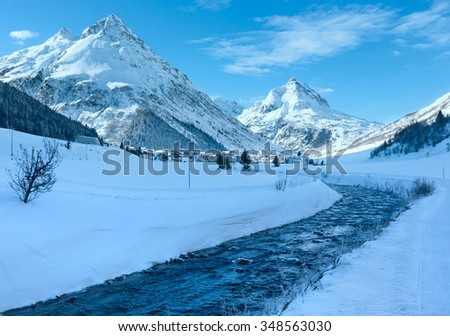 Winter mountain stream view and village in valley (Austria).
