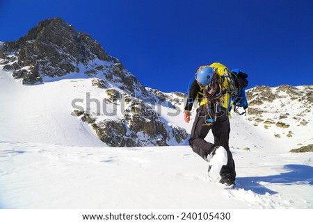 Winter mountaineer climbs to the snow covered summit - stock photo
