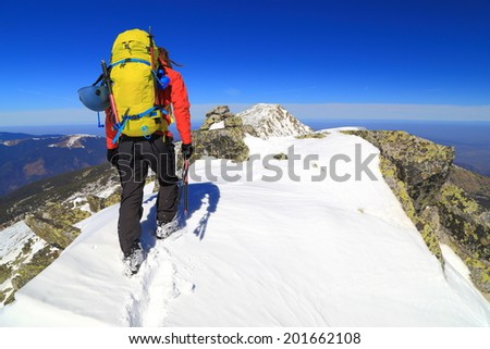Winter mountaineering on sunny day with climber reaching the summit