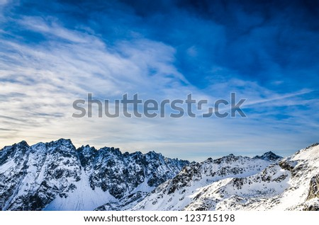 Winter mountains landscape with dark blue cloudy sky - stock photo