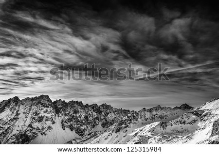 Winter mountains landscape with dark cloudy sky, monochrome vintage view - stock photo