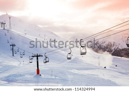 Winter mountains panorama with ski slopes and ski lifts on a cloudy day - stock photo