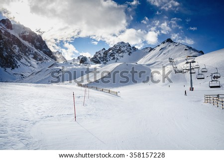Winter mountains panorama with ski slopes and ski lifts. Skiers going down the slope under ski lift. - stock photo
