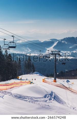 Winter mountains with ski slopes and ski lifts  - stock photo