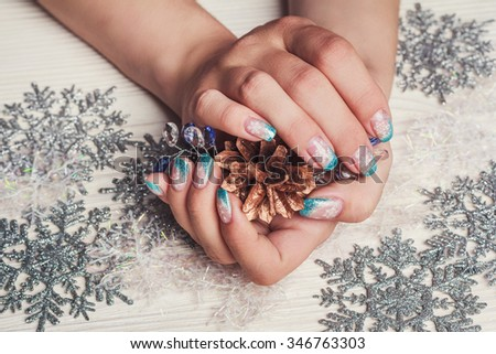Winter nail art with snowflakes and light blue french on wooden background