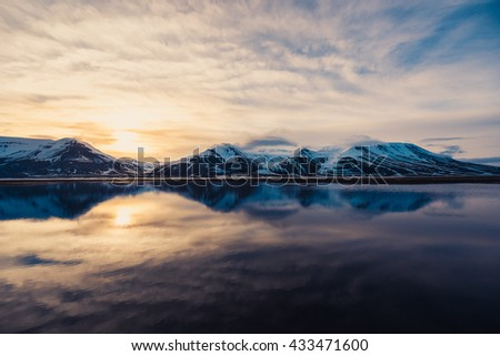 winter nature snow-capped mountains of Svalbard, Longyearbyen, Spitsbergen, Norway at the time of fire rolled reflection ocean wallpaper - stock photo