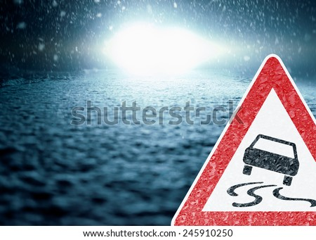 Winter Night Driving - Winter Road - Caution Sleekness - Abstract winter background with warning sign - Snow covered road at night. - stock photo