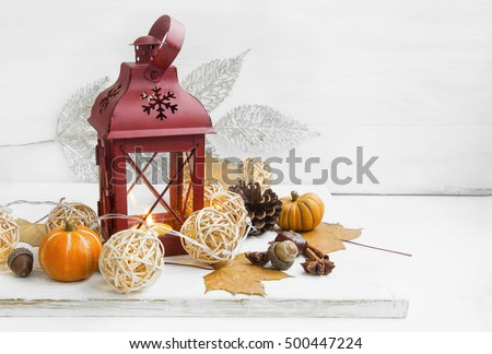 Winter or autumn candle lantern with lights balls decoration on white background