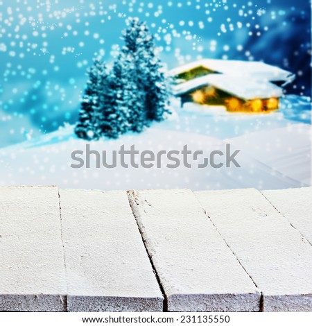 Winter or Christmas advertising background with empty white painted rustic wooden boards overlooking a lighted snowy timber mountain cabin with falling snow for product placement - stock photo