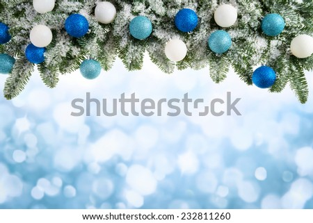Winter or Christmas background composed of an arch of fresh snowy fir branches and bokeh lights, with light blue copyspace - stock photo