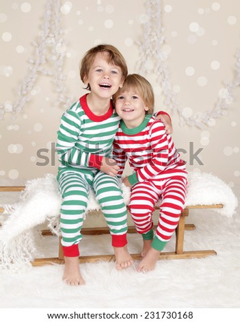 Winter or Christmas Holidays: laughing, smiling, happy kids in red and green striped pj pajamas on wood sled in fake snow, snowflakes