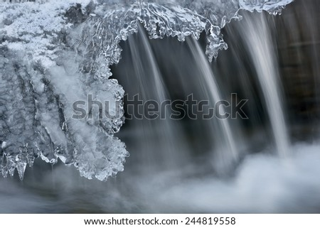Winter Orangeville Creek cascade framed with icicles and captured with motion blur, Michigan, USA - stock photo