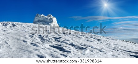 Winter ountain top panorama view on blue sunshine sky background.