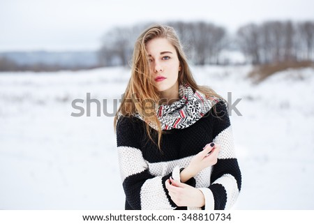 winter outdoor portrait of cute attractive beautiful sensitive young blond girl with long hair with black and white striped sweater with red lipstick looking to camera on natural cloudy background - stock photo