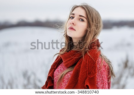 winter outdoor portrait of cute young attractive serious blond girl with red sweater and scarf looking to camera on natural field background. Cloudy weather - stock photo