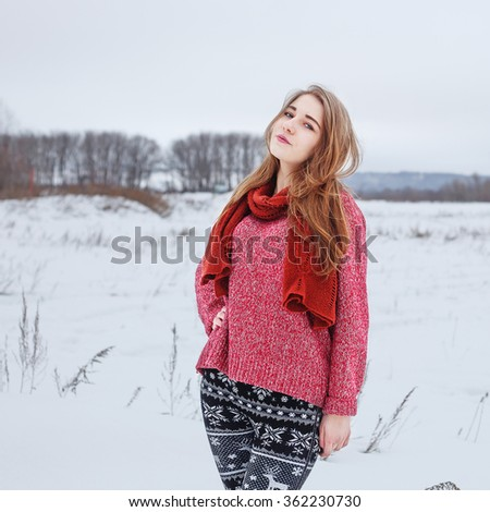 winter outdoor portrait of cute young pretty blond girl with red sweater and scarf looking to camera on natural field background. Cloudy weather. Lifestyle