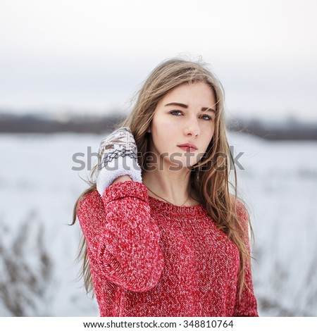 winter outdoor portrait of cute young pretty serious girl with red sweater and white mittens looking to camera and fixing hair on natural field background. Cloudy weather. Lifestyle - stock photo