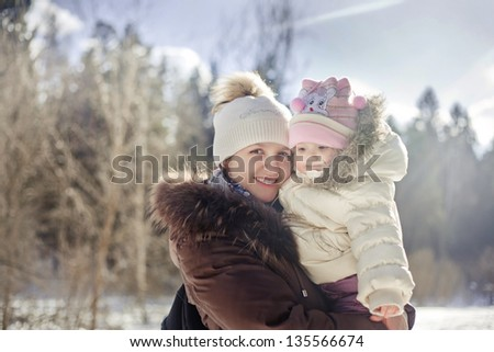 Winter outdoor portrait of mother and baby - stock photo