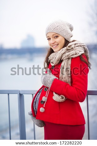 Winter outdoor portrait of pregnant woman in fashionable clothes standing by the river