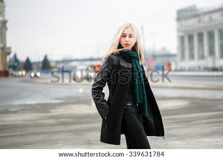 Winter outdoor portrait of young serious girl on urban street background