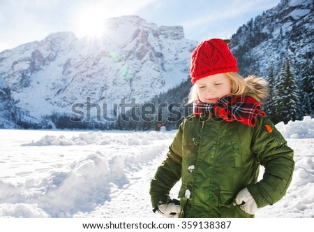 Winter outdoors can be fairytale-maker for children or even adults. Happy child in green coat standing in the front of snowy mountains