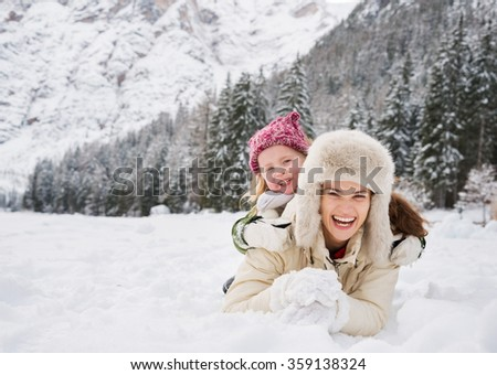 Winter outdoors can be fairytale-maker for children or even adults. Portrait of happy mother and child outdoors in front of snowy mountains - stock photo