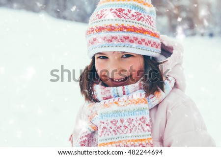 Winter outdoors portrait of cute adorable girl with knitted cap, scarf and hood smiling and looking at camera. Cold weather and falling snow flakes.
