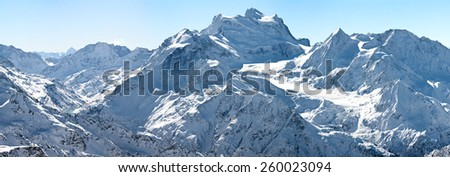 winter panorama of high alpine mountains with lake and glacier - stock photo