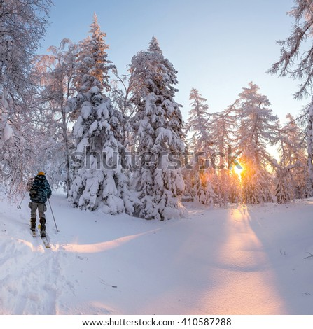 Winter panoranic landscape. Tourist in snowshoeing in jacket standing on the hill