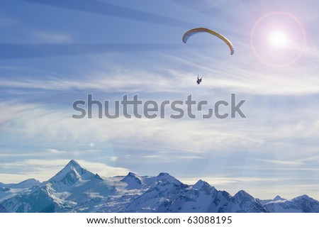 winter paragliding in alps mountains over high peaks and valley - stock photo