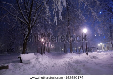 Winter park with red benches covered with snow in the evening. - stock photo