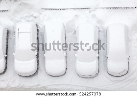 Winter parking lot with line of cars covered with snow, top view