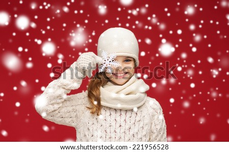 winter, people and happiness concept - smiling girl in hat, scarf and gloves with big snowflake - stock photo