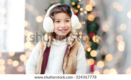 winter, people, childhood and happiness concept - happy little girl wearing earmuffs over christmas tree lights background - stock photo