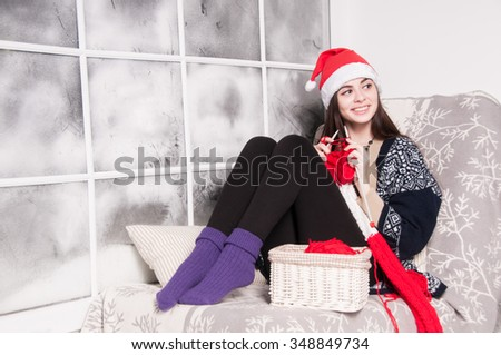 winter, people, happiness concept - attractive beautiful young woman knitting a scarf - stock photo