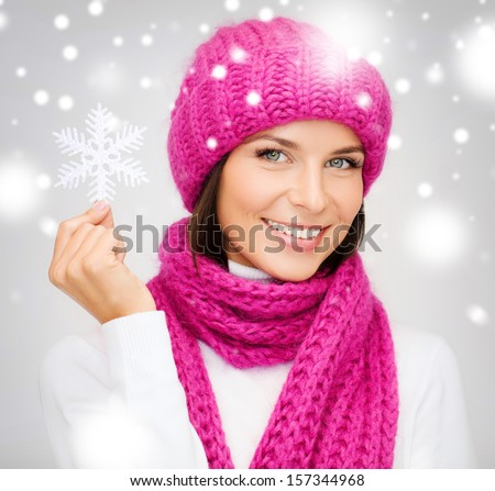 winter, people, happiness concept - woman in hat and muffler with big snowflake