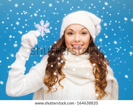 winter, people, happiness concept - woman in hat, muffler and gloves with big snowflake