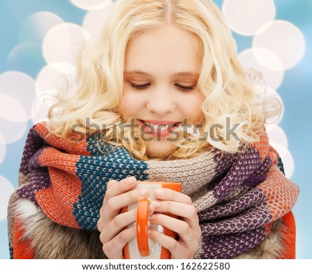 winter, people, happiness, drink and food concept - smiling teenage girl in warm clothes with tea or coffee mug - stock photo